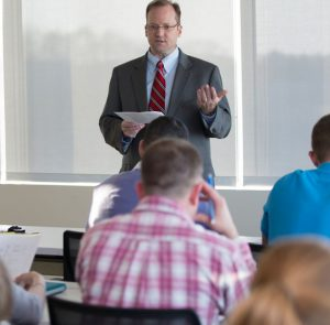 Middle-aged man in professional attire addressing students.